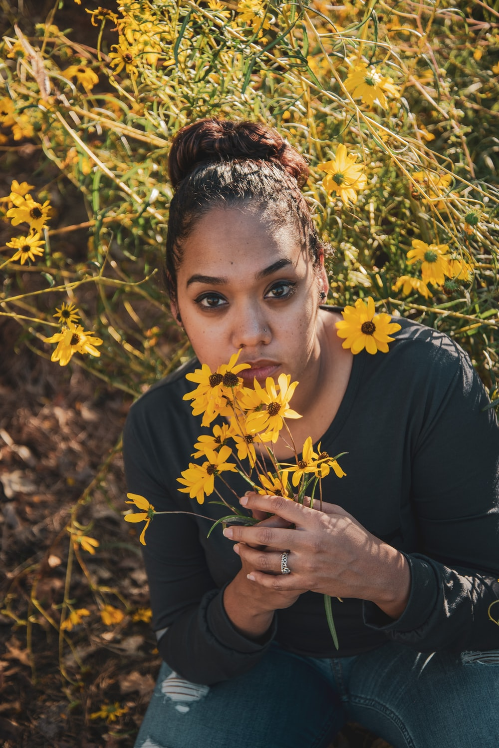 woman in black shirt holding yellow flowers
