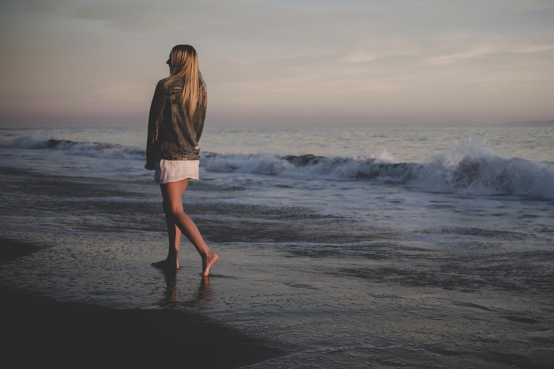 woman walking on seashore under gray sky