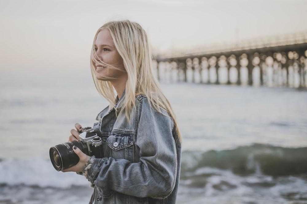 woman holding camera standing on seashore