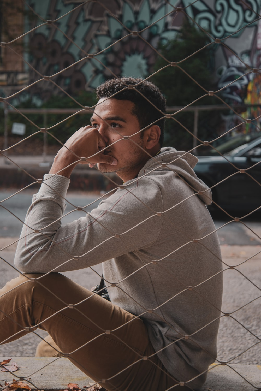 man sitting beside fence with hand on face outdoors during daytime