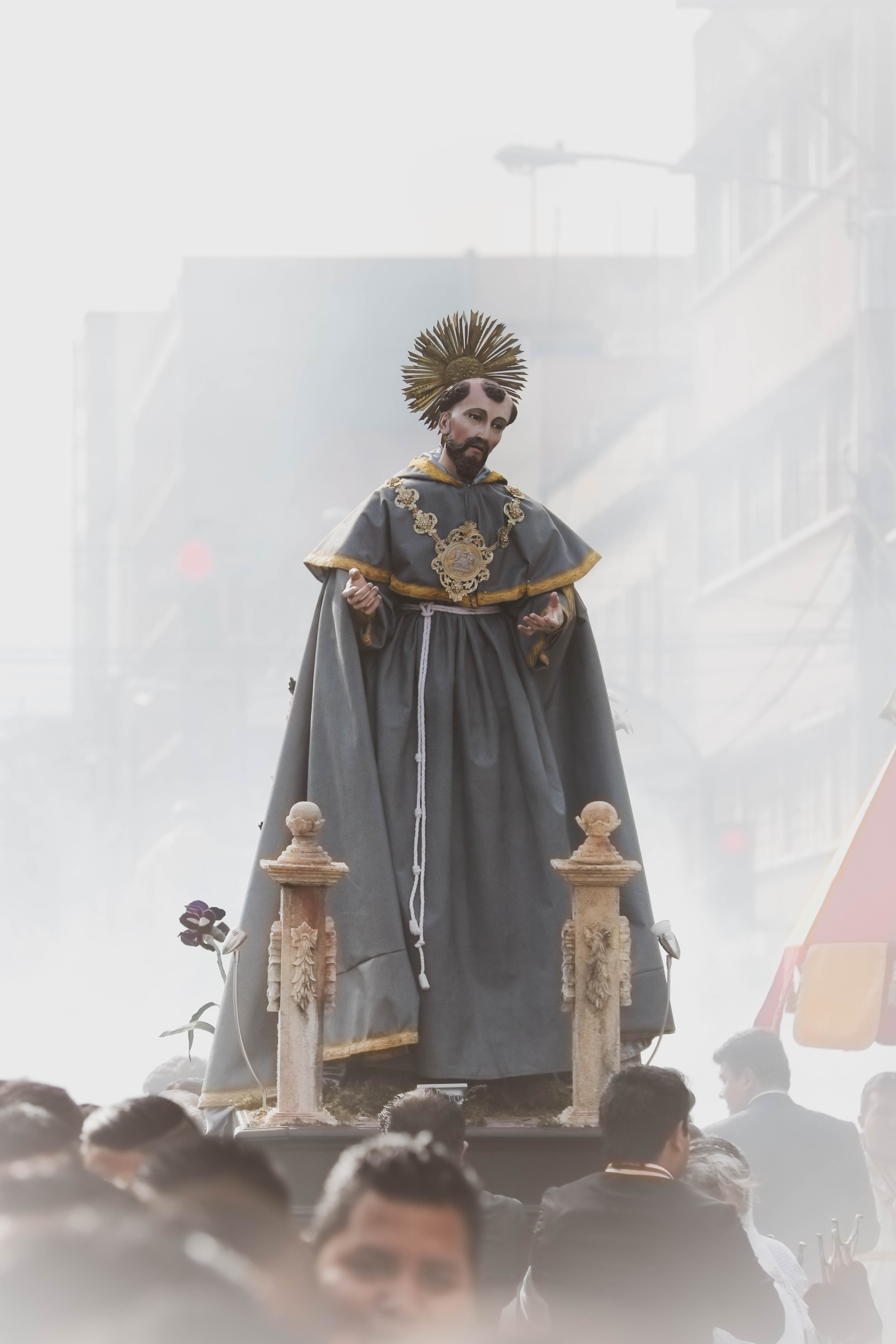 man in grey and yellow robe religious statuette being carried by people
