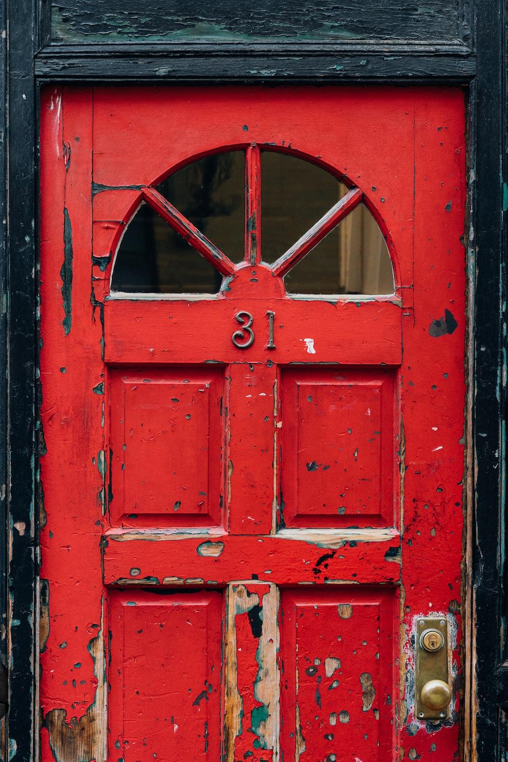 red wooden door with brass doorknob