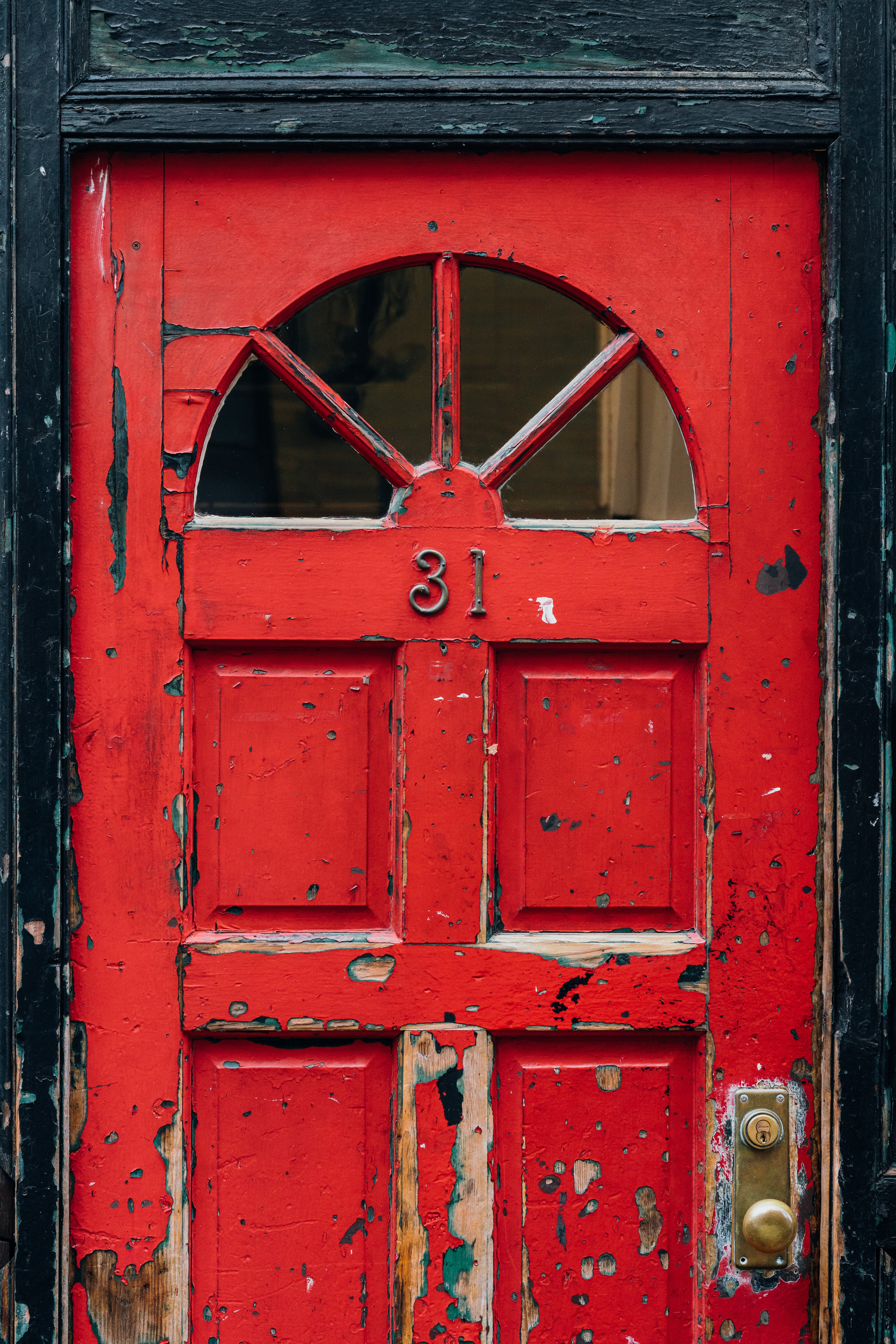 red wooden door with brass doorknob