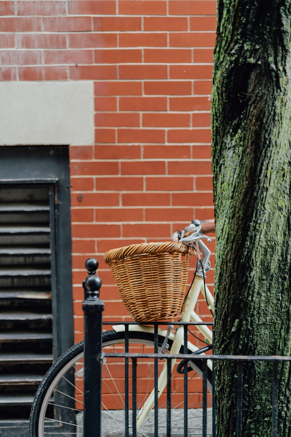bicycle with woven basket parked beside the street