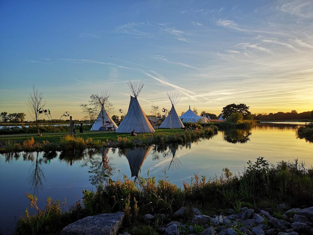 tipi tents on grass field near stream