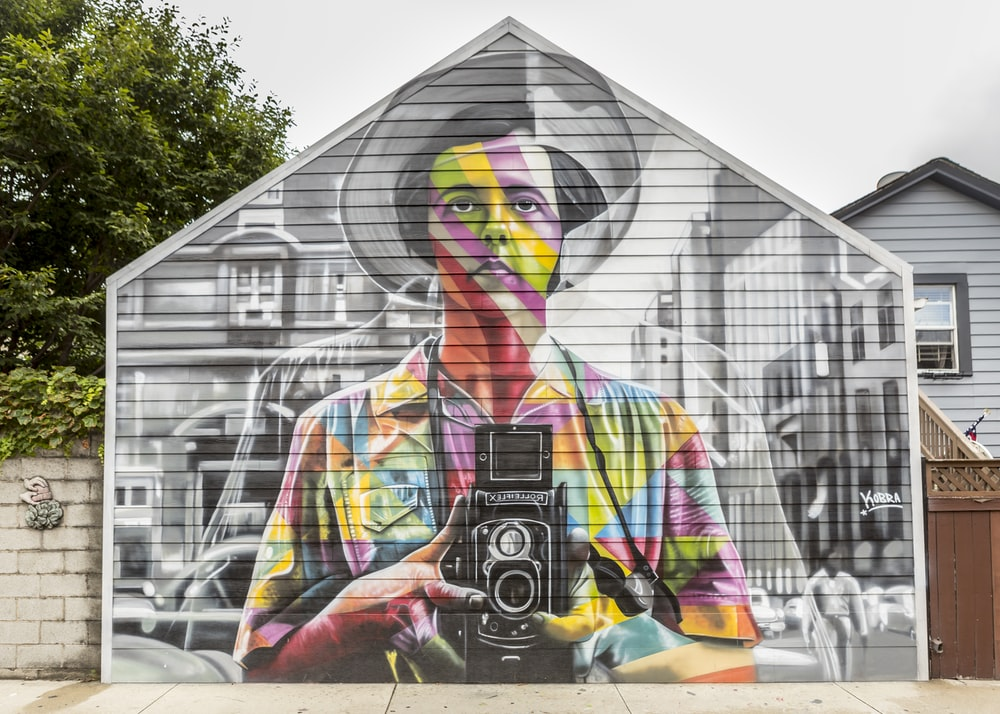 man holding camera painting on side of house