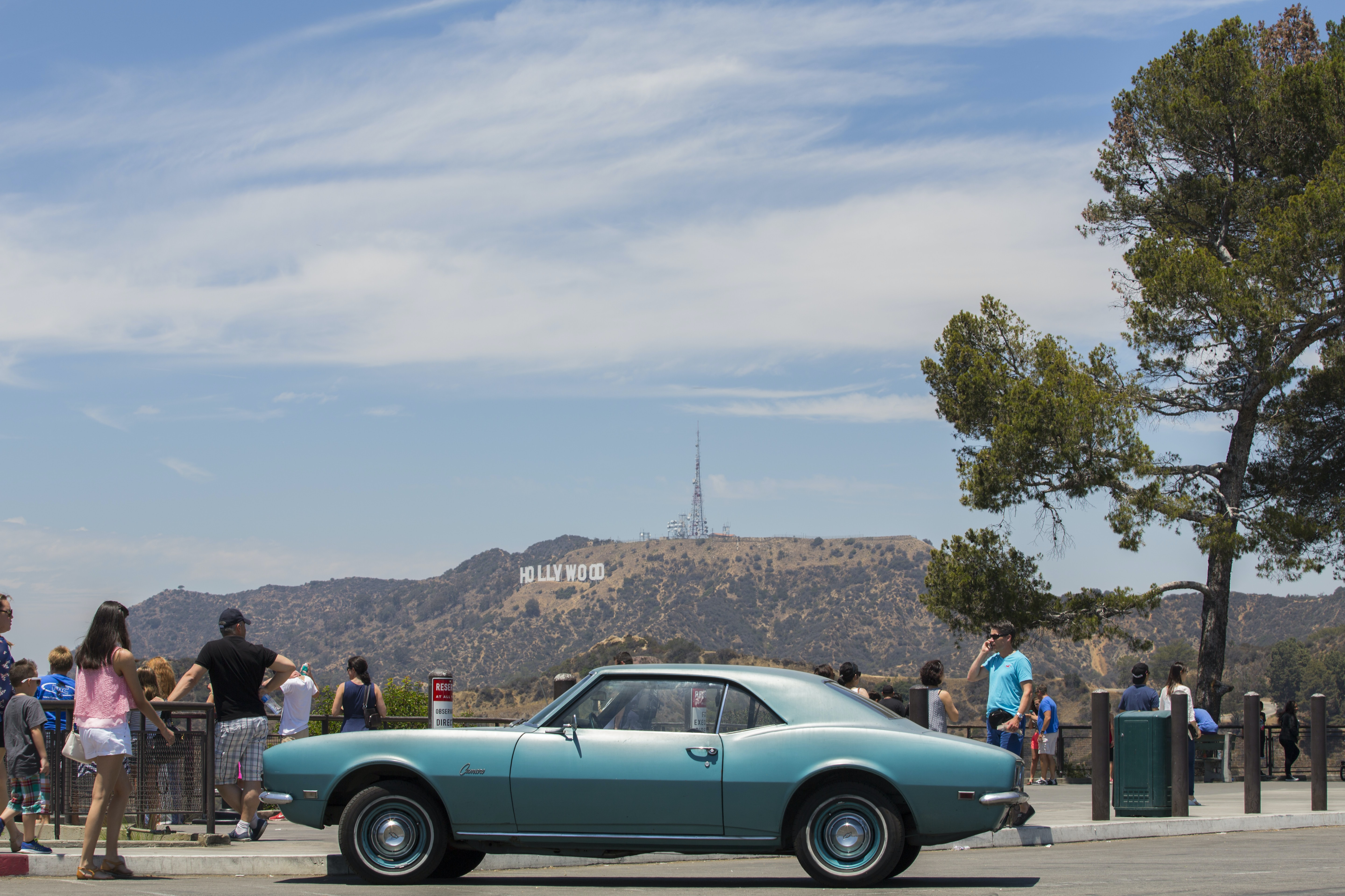 classic blue coupe on road beside people at near Hollywood sign at California during daytime