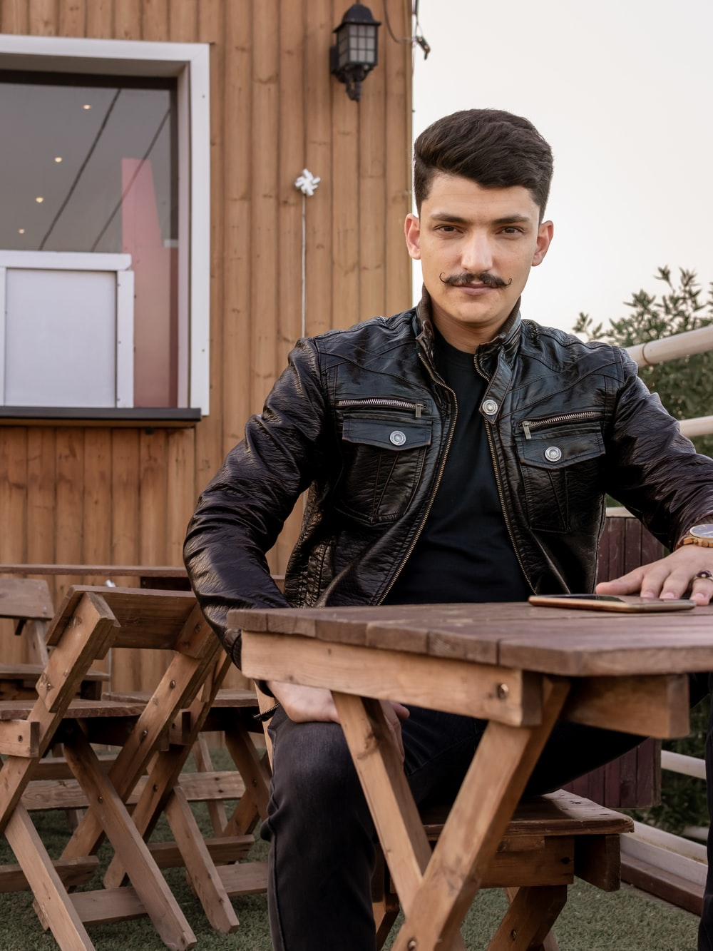 man sitting at table outdoor during day