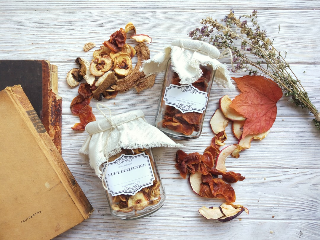 Rustic autumn composition with dried fruits in a glass jars and vintage labels on white wood background, harvest concept, healthy preserved food. Top view