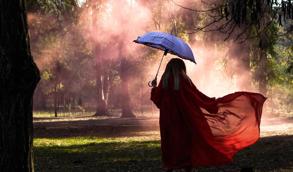 woman holding blue umbrella