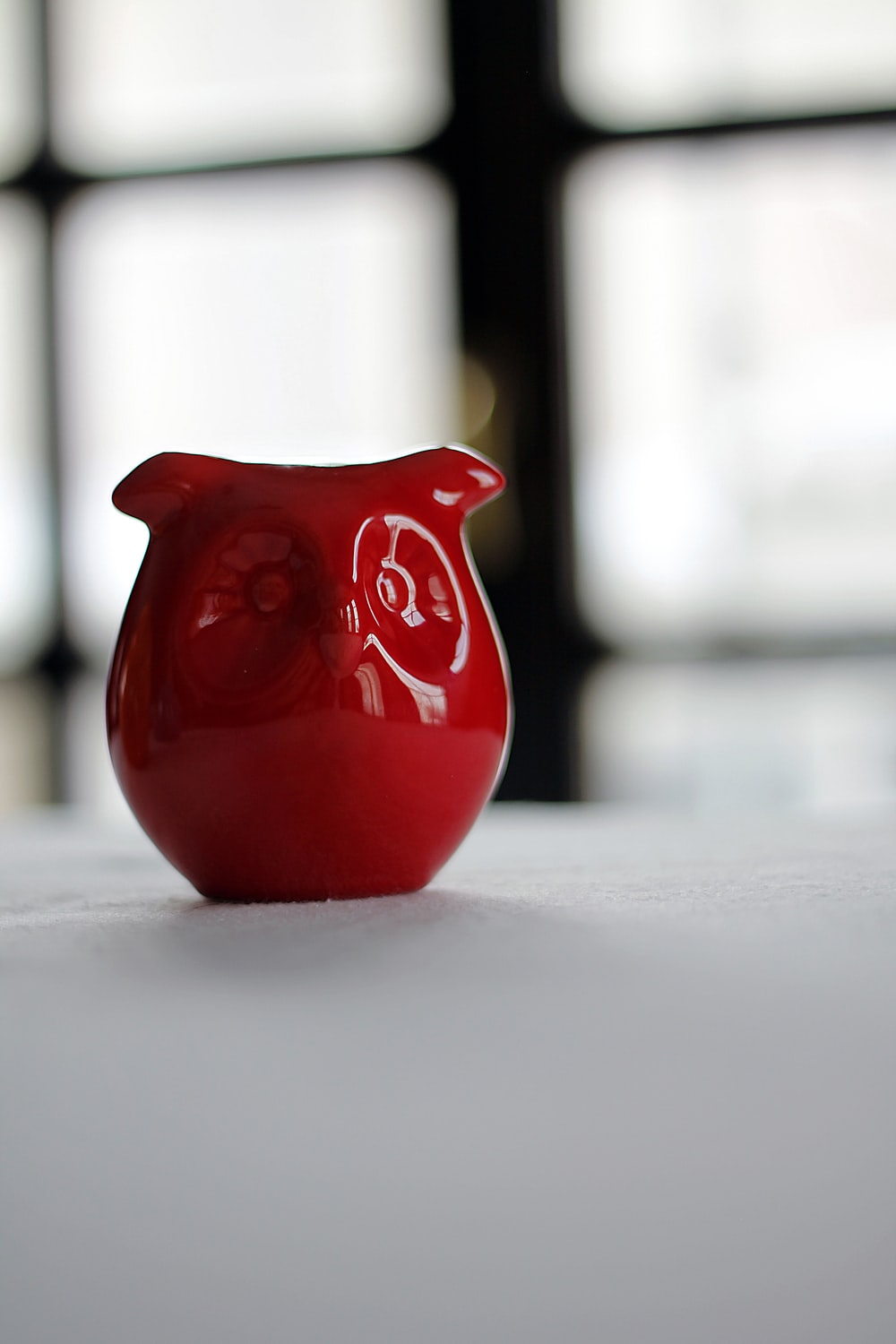 red owl figurine on white surface