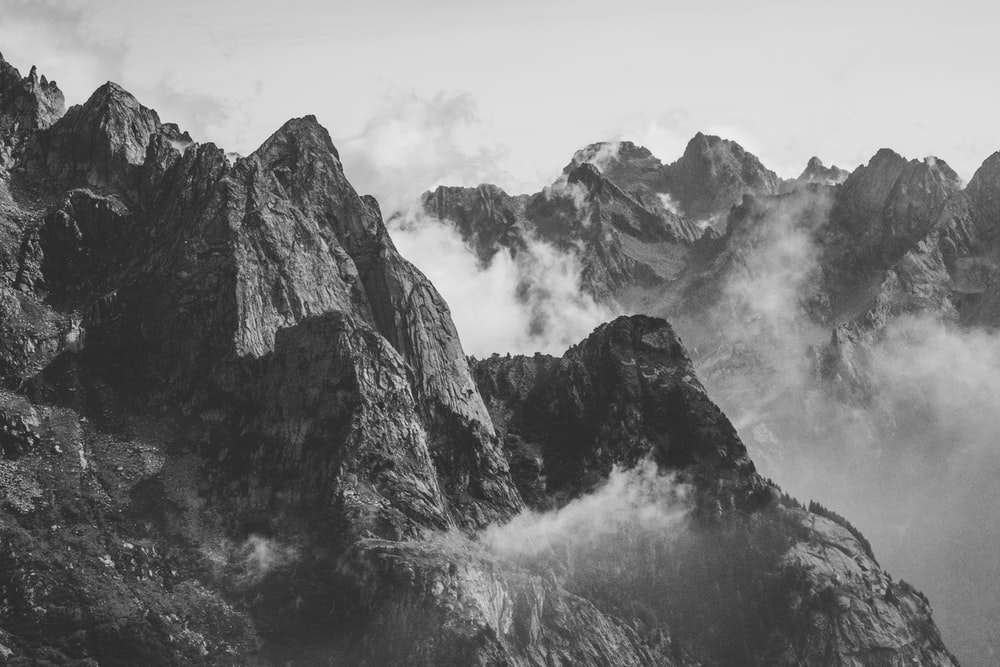 grayscale photography of mountain with smoke