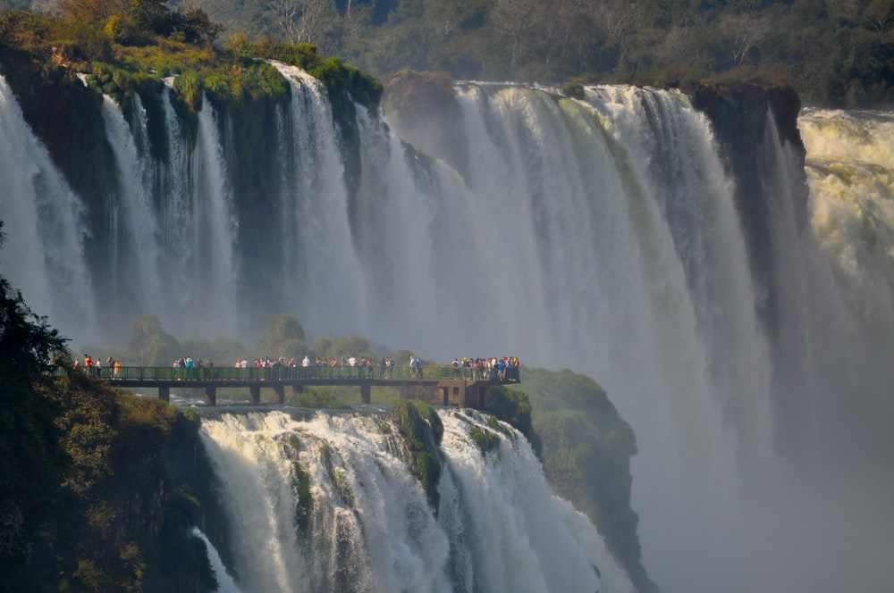 people looking at large waterfall