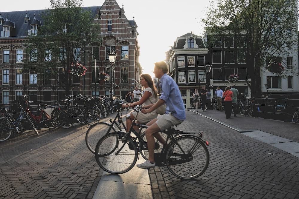 man and woman biking along city at daytime
