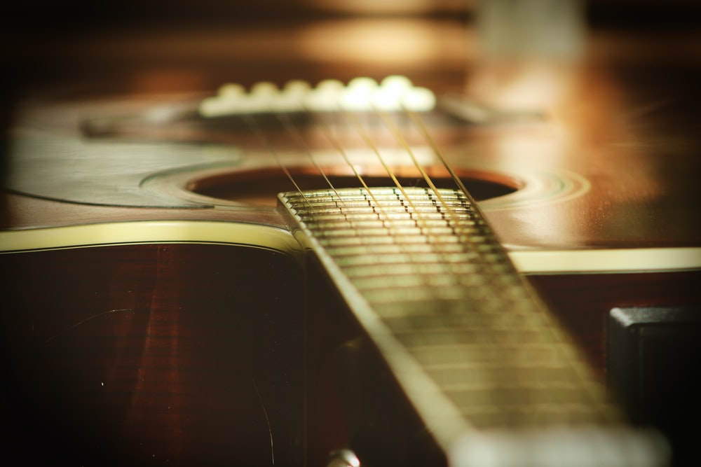 selective focus photography of wooden classical guitar