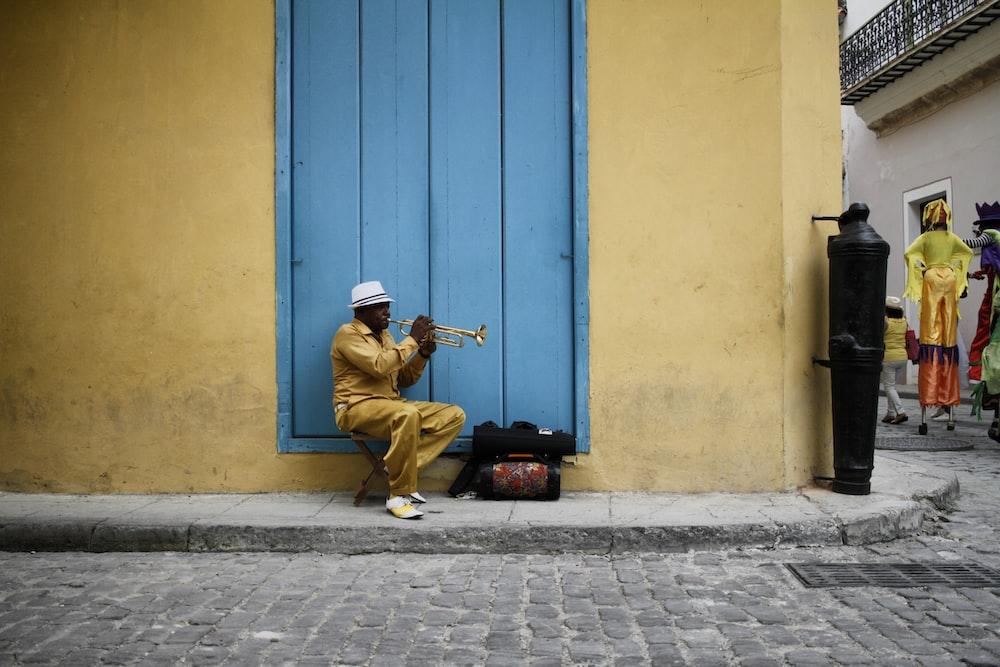 sitting man wearing yellow shirt during daytime