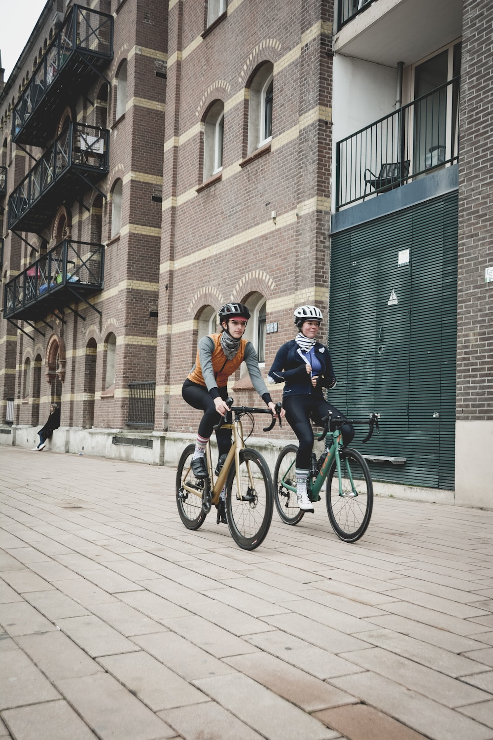 two person riding on bicycles beside building