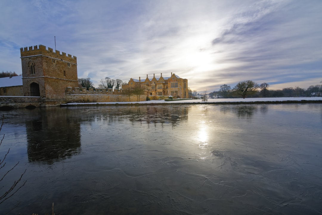 """Broughton castle lies in a """"frost hollow"""" and frequently sees extreme cold which causes the moat to freeze. See here in weak early morning sun shine with 14th century buildings reflected in the moat.  The local Cotswold iron stone gives the building and attractive honey coloured glow."""