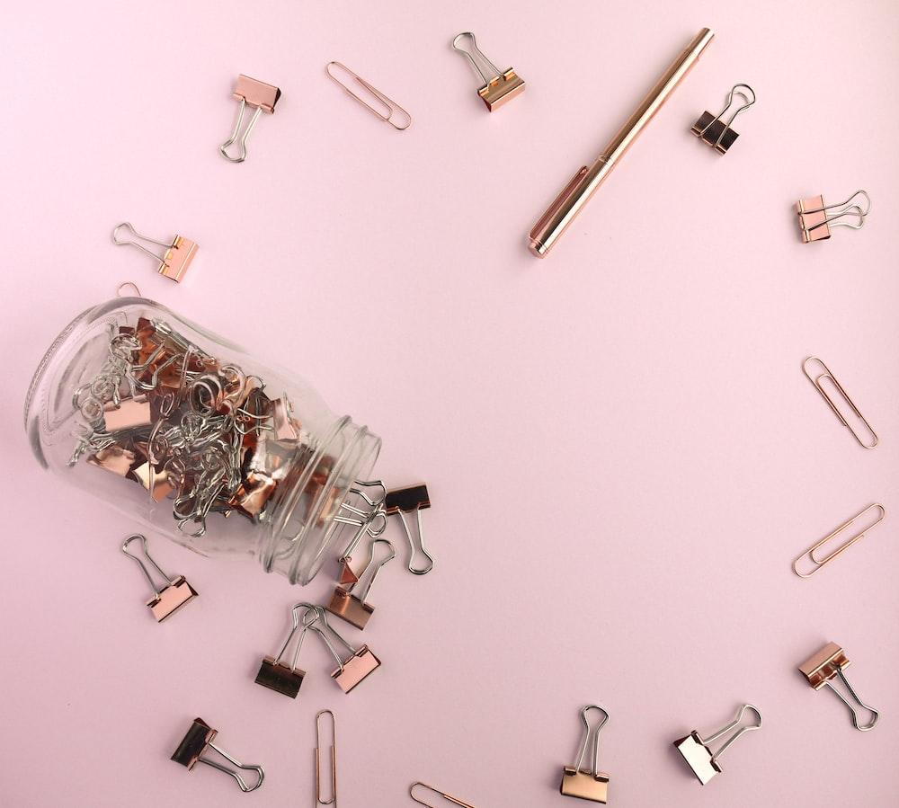 assorted-color folder clip lot on pink surface