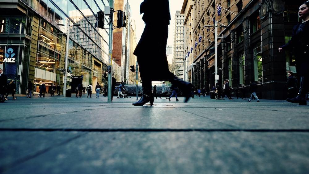 woman in black dress walking on side walk
