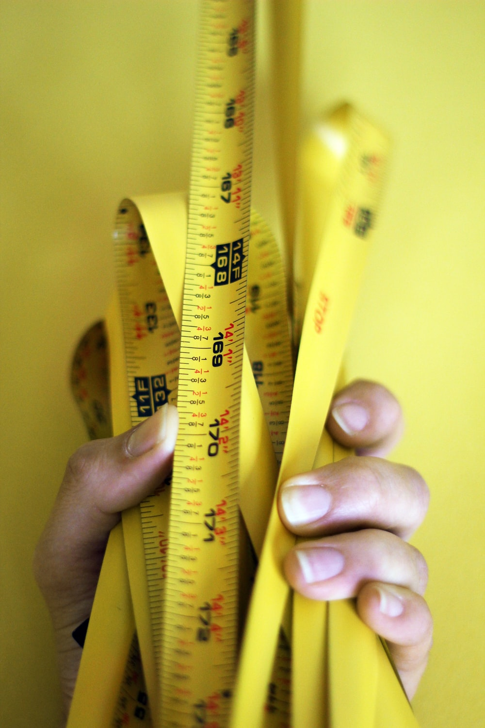person holding yellow steel tape measure