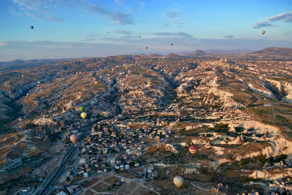 aerial photography of village with hot air balloon flying on sky