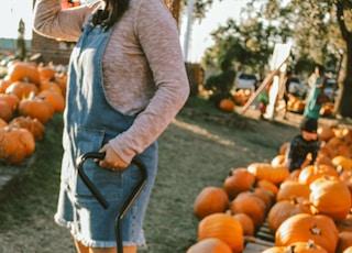 woman standing between pile of pumpkins during daytime
