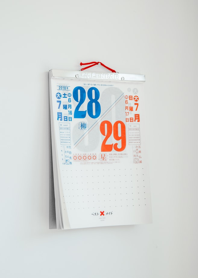 A photo of a white wall with a calendar hanging on it. The calendar is mostly white with orange and blue.