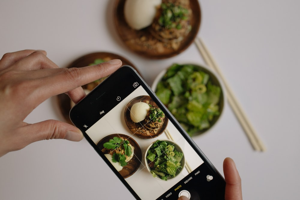 person taking picture of vegetables