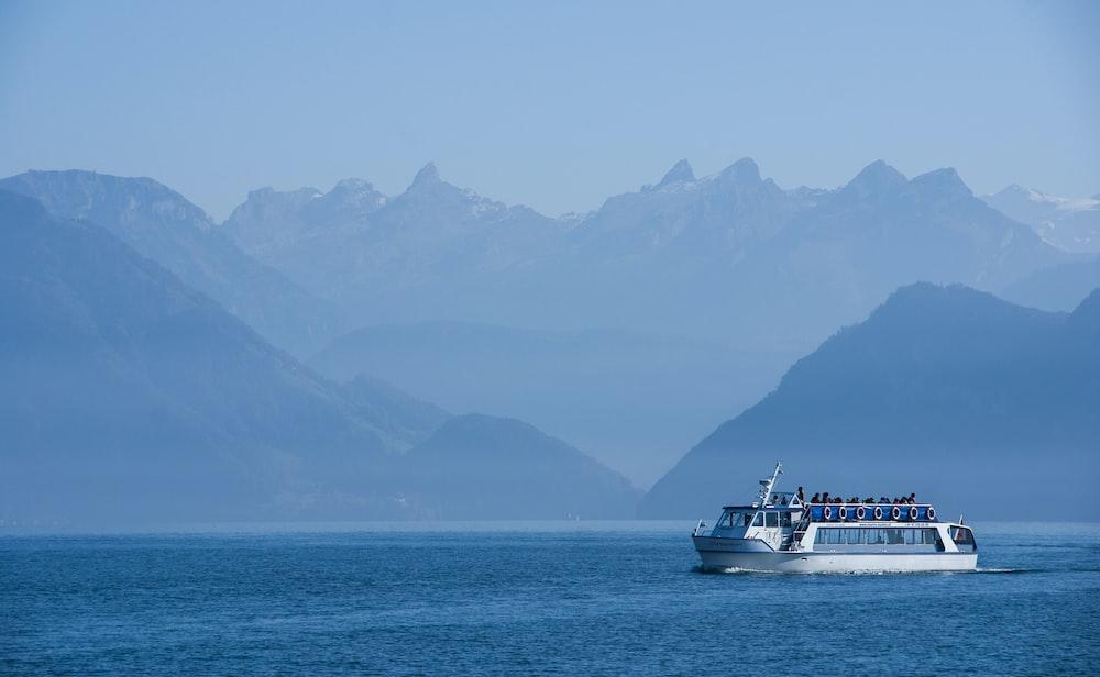 white ferry sailing at sea near mountainous shore