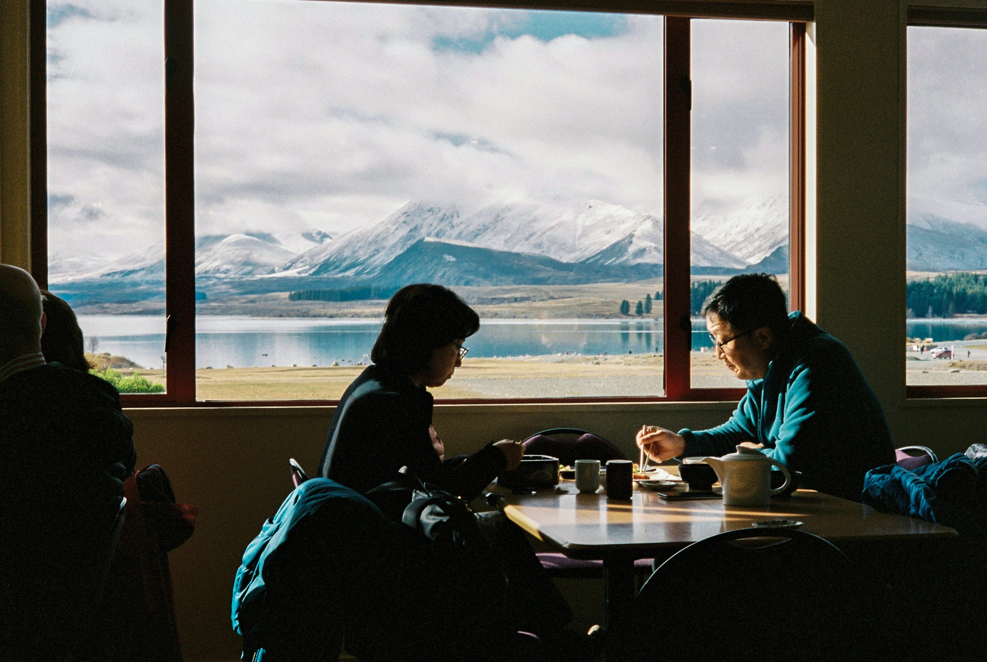 Lunch with a view. A tourist couple eating lunch at a Japanese restaurant next to Lake Tekapo, New Zealand.