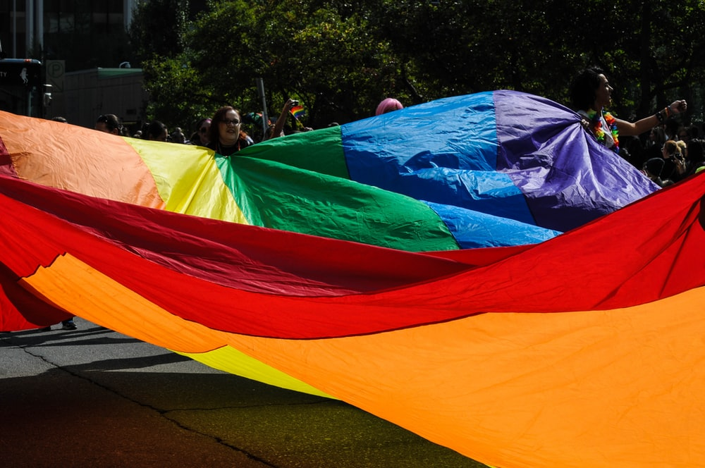people holding multicolored tarpaulin during daytime