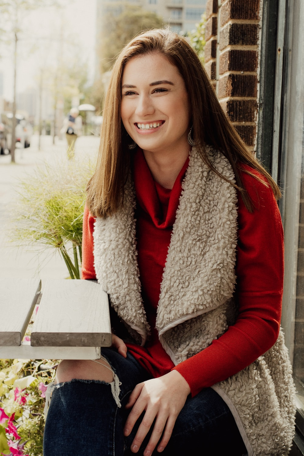 woman in red sweater sits beside table and smiling