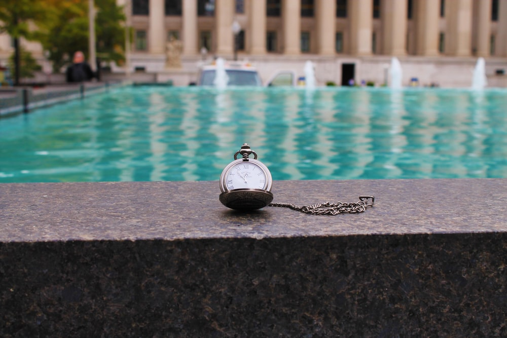 silver pocketwatch on pool