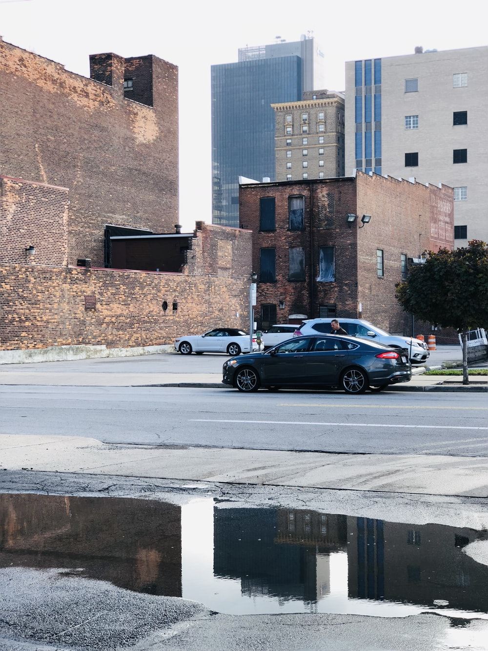 gray sedan parked on roadside near parking lot during daytie