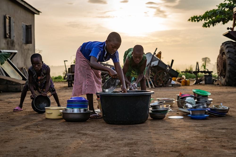 children washing dishes outside