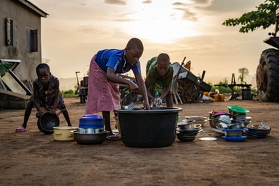 children washing dishes outside togo teams background