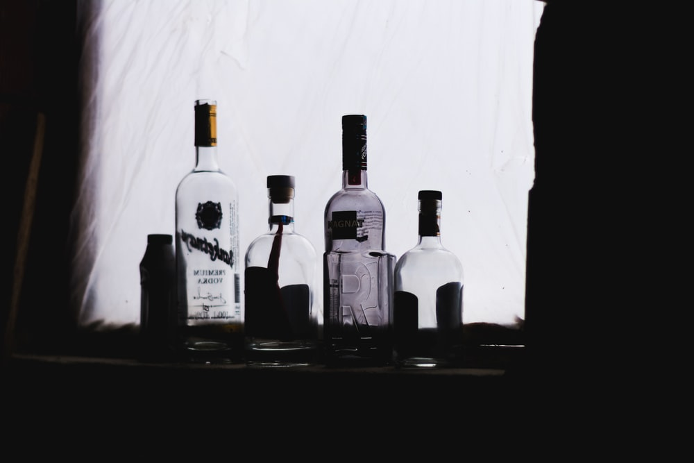 four clear glass bottles in dim light