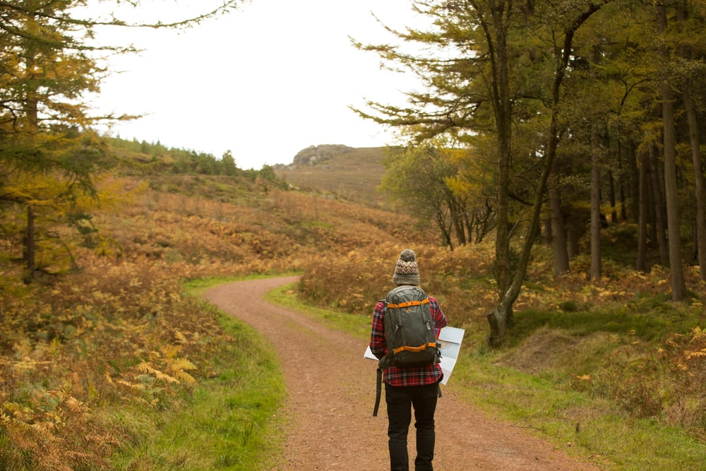 person standing on pathway holding white paper
