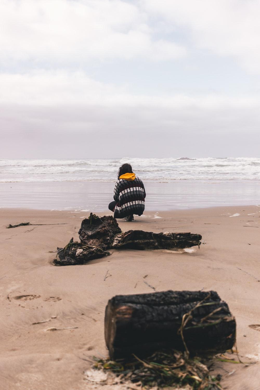 person kneeling on seashore