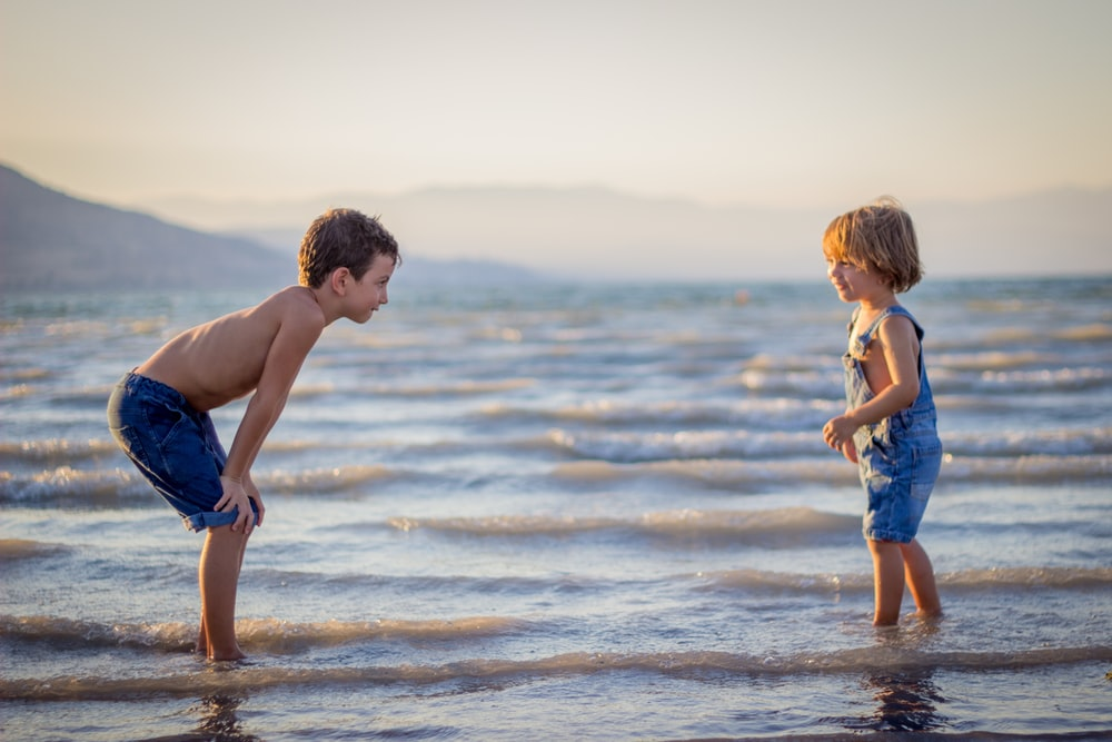 boy bending knee while watching younger child on beach
