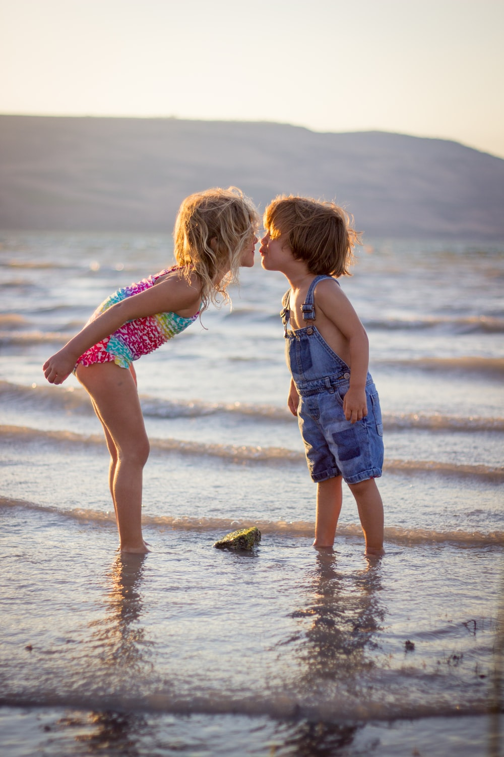 girl and boy kissing on beach during daytime