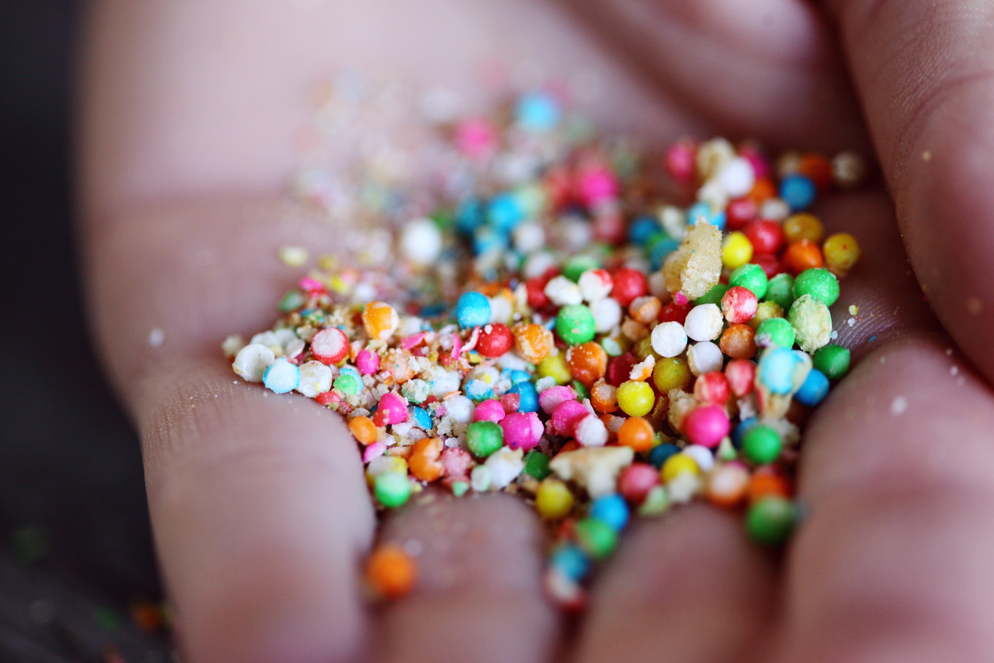Handful of cookie crumbs and rainbow colored sugar candies.