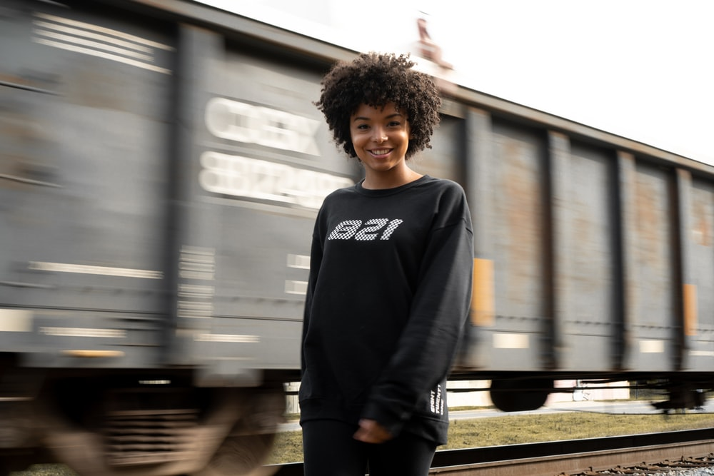 smiling woman in black sweater stands beside passing train