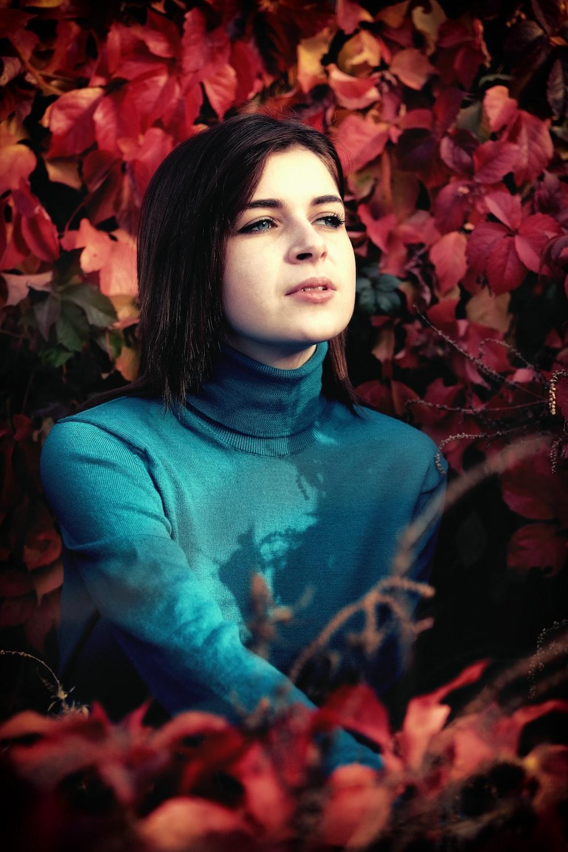 woman sitting near red flower