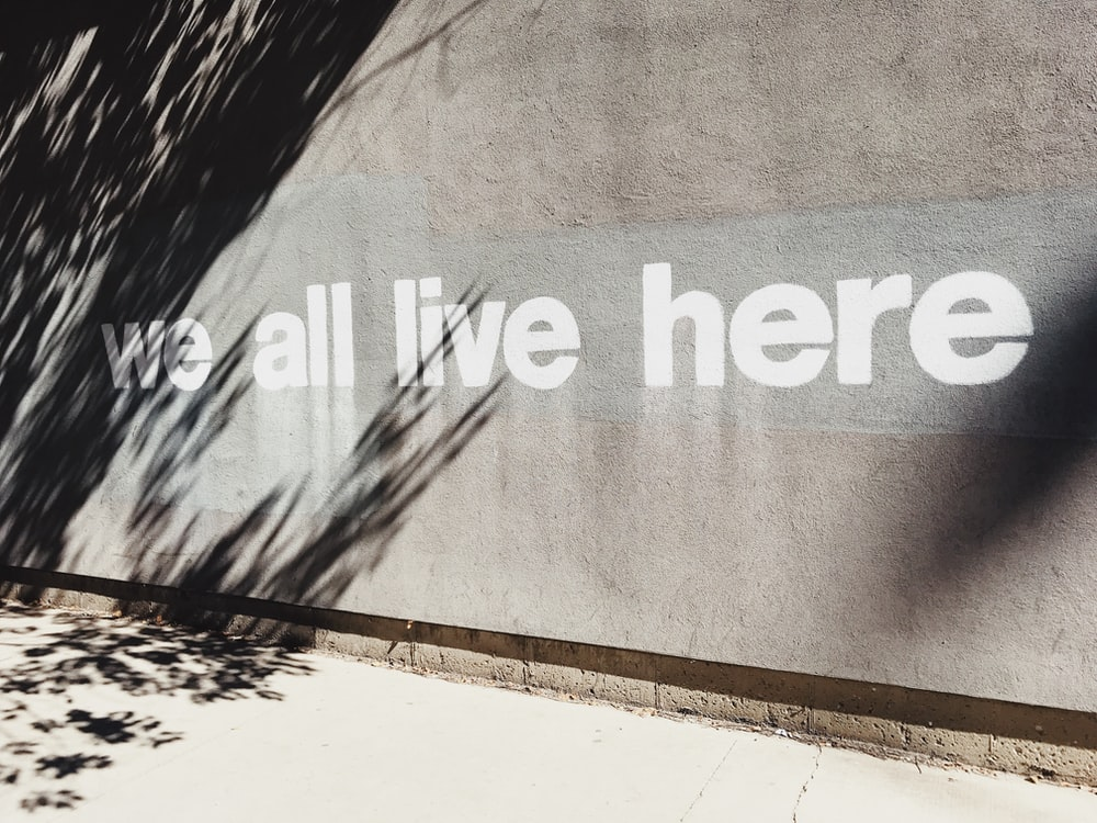 gray wall with we all live here graffiti