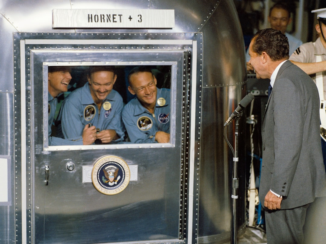 On July 24, 1969, President Richard Nixon welcomes the quarantined Apollo 11 astronauts, Neil Armstrong, Michael Collins, and Buzz Aldrin, aboard the U.S.S. Hornet after the historic Apollo 11 lunar landing mission.