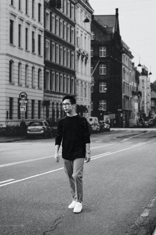 man walking on road by buildings
