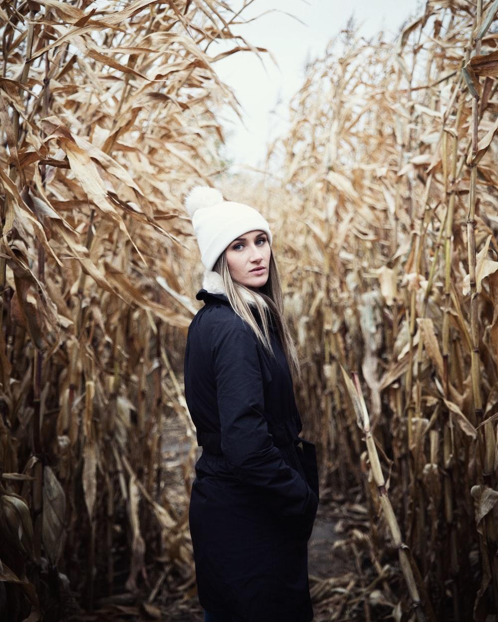 woman in black jacket at cornfield