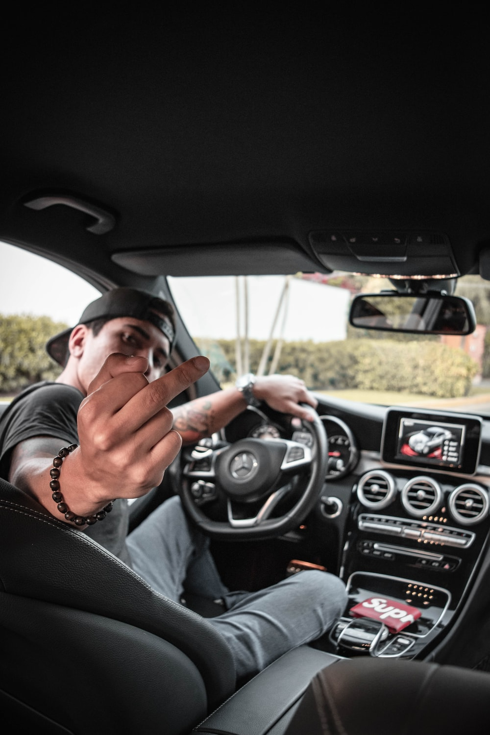 man behind car steering wheel showing his right middle finger